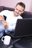 Sofa d'hommes avec l'utilisation de téléphone et d'ordinateur. Photographie stock