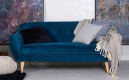 Sofa de bleu marine rétro avec les coussins et la couverture grise images stock