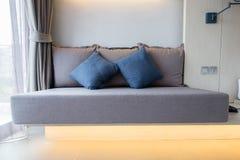 Sofa de Brown avec les oreillers bleus dans la chambre à coucher Images libres de droits