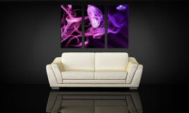 Sofa and decorative canvas panel. White leather couch under three decorative canvas panel Stock Images