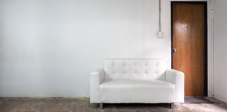 Sofa des weißen Leders und weiße alte Wand Stockfoto