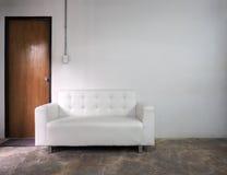 Sofa des weißen Leders und weiße alte Wand Stockfotos