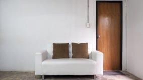 Sofa des weißen Leders und weiße alte Wand Stockfotografie