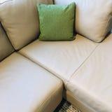 Sofa faisant le coin gris avec le coussin vert photos stock