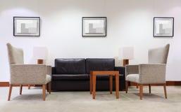 Sofa, fauteuils et table dans le bureau vide Image stock