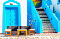 Sofa in front of Greek house painted with blue Stock Photos