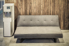 Sofa furniture and water cooler on wood texture Royalty Free Stock Photo