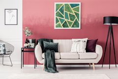 Sofa and geometric painting. White sofa with blanket and pillows and green, geometric painting on red wall in living room interior Stock Images