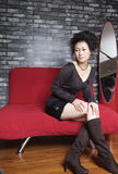 Sofa and girls. Beautiful Chinese girl sitting on a red sofa Stock Images