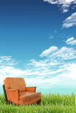Sofa on the grass field. Comfortable leather sofa in a green grass meadow Royalty Free Stock Images