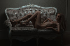 On the sofa lay naked girl. Royalty Free Stock Images