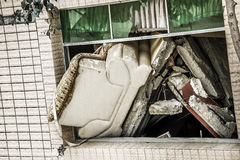 Sofa leaning out of a broken window from collapsed house Stock Photo