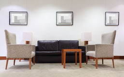 Sofa, Lehnsessel und Tabelle im leeren Büro stockbild