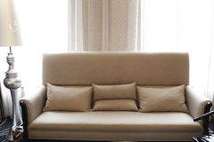 The sofa of light color close to the window Royalty Free Stock Images
