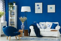 Sofa in living room. White sofa in blue living room with porcelain accessories Stock Images