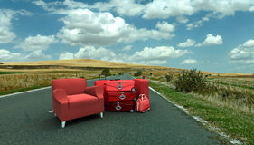 Sofa and luggage in the middle of the road. Red sofa and a pile of luggage in the middle of a country road Royalty Free Stock Image