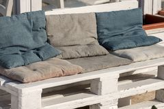 Sofa Made of Wooden Pallet. Sofa made of white wooden pallet and cushions of cloth. Outdoor setting Royalty Free Stock Image