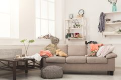 Sofa in messy room. Sofa in messy living room with many stack of clothes. Disorder and mess at home, copy space royalty free stock image