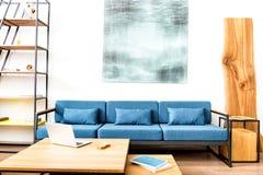 Sofa mit Bild über und Bücherschrank im Raum Lizenzfreies Stockfoto