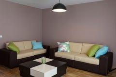 Sofa mit drei Kissen und Tabelle Lizenzfreie Stockfotografie