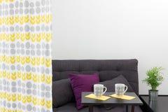 Sofa mit Kissen hinter einem dekorativen Vorhang stockbilder