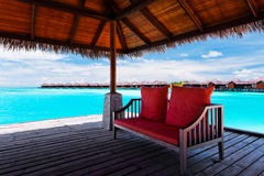 Sofa mit roten Kissen auf Anlegestelle in der tropischen Lagune Stockbilder