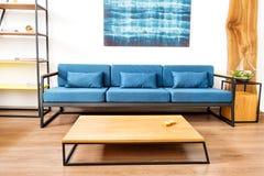 Sofa mit Schreibtisch und Bild über ihm im geräumigen Raum Stockbild