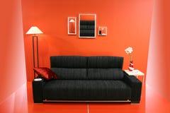 Sofa noir sur le mur rouge photographie stock