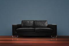 Sofa noir sur le plancher en bois avec le mur bleu Photographie stock libre de droits