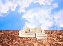 Sofa onstone floor and in the sky. For background Stock Photo