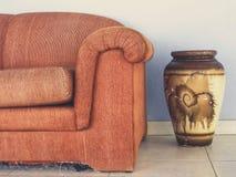 Sofa orange. Sofa and earthenware pot in interior Stock Photos