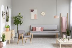 Sofa with pastel pink cushions in real photo of grey living room. Interior with retro armchair, fresh green plants, simple poster and blanket hanging on ladder royalty free stock image