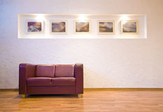 Sofa and pictures. A red leather sofa standing alone at the wall, five pictures in the wall recess, hardwood floor Royalty Free Stock Image
