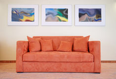 Sofa and pictures. An orange sofa standing alone at the wall of a hotel room, three pictures on the wall, carpeted floor Royalty Free Stock Photography
