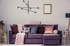 Sofa and pillows. Modern lamp and violet sofa decorated with patterned pillows in a living room interior royalty free stock photos