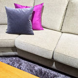 Sofa with purple cushions on a fluffy carpet Royalty Free Stock Photo