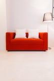 Sofa rouge avec la lampe d'oreiller et de lumière Photo stock