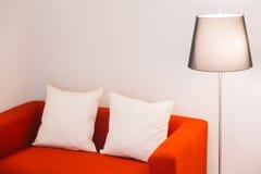 Sofa rouge avec la lampe d'oreiller et de lumière Images stock