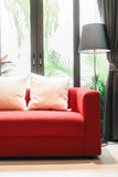 Sofa rouge avec la lampe d'oreiller et de lumière Image stock