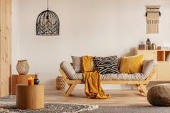Sofa scandinave avec les oreillers et la couverture jaune foncée dans le salon lumineux intérieur avec le lustre noir photos libres de droits