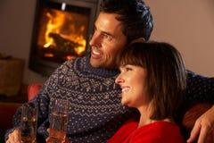 Sofa se reposant âgé moyen de couples par le feu de bois confortable image libre de droits