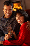 Sofa se reposant âgé moyen de couples par le feu de bois confortable Image stock