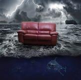 A sofa on the sea. In mezzo ad un oceano in tempesta divano galleggia sopra un branco di squali Stock Images