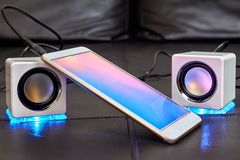 Two speakers with blue LEDs are connected to smartphone. On the sofa seat there are two speakers with blue LEDs, which are connected to smartphone with cable royalty free stock image