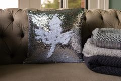 Sofa with sequin cushion with leaf motif. And warm winter rugs royalty free stock photo