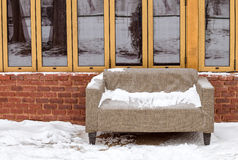 Sofa in the snow near a brick wall with windows Stock Photos