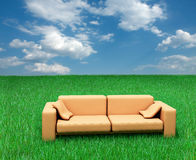 Sofa sur l'herbe et le ciel nuageux image stock