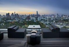 Sofa sur la terrasse donnant sur le parc et le bâtiment verts, Bangkok, Thaïlande Photographie stock