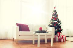 Sofa, table and christmas tree with gifts at home Stock Photography