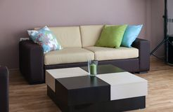 Sofa with three pillows and table Royalty Free Stock Photography